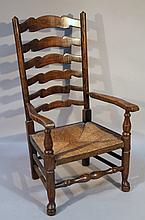 A 19thC elm rush seated chair, with a ladderback and turned front stretcher, 100cm high.
