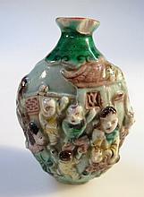A Chinese Cantonese earthenware snuff bottle, of shouldered form, raised with many figures, polychro