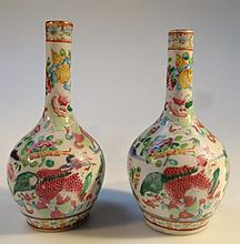 A pair of Chinese famille vert bottle vases, each of shouldered form with cylindrical stems gilt highlighted and polychrome decorated with buildings, flowers, dragons and foliage, predominately in blue, green and pink, on circular feet, late Qing per