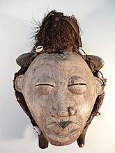 A Gabon Purio African tribal mask, with a carved wood central face, with feathered and shell head dr