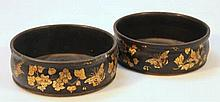 A pair of papier mache coasters, each raised with