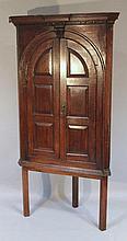 An oak corner cupboard, with an inverted fixed de