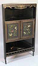 A black lacquer corner cabinet, the carved cornic