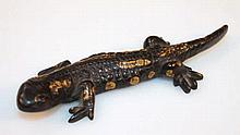 A cold painted bronzed figure, of a lizard in bla