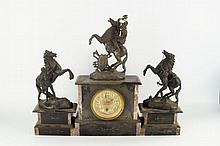 A slate and marble clock garniture, surmounted by cast Romanesque figures.