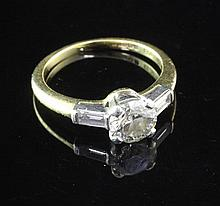 An 18ct gold and platinum single stone diamond ring with baguette cut diamond set shoulders, size K.