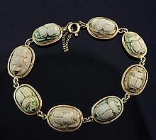 An 18ct gold and Egyptian faience scarab bracelet, 7in.