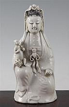 A Chinese white glazed porcelain figure of Guanyin holding a child, Jiaqing period, 21cm, child's head re-stuck