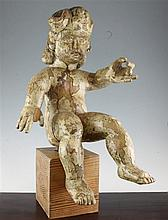 A 19th century Spanish painted pine figure of a seated putto, 22in.