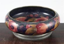 A William Moorcroft pomegranate pattern Tudric pewter mounted bowl, c.1920, 22cm, mount loose