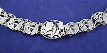 An Edwardian Art Nouveau silver belt, overall length 31in.