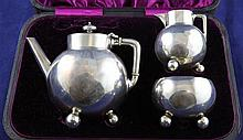 A cased stylish Victorian silver three piece bachelor's tea set by Walter & John Barnard, gross 10 oz.