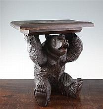 An early 20th century Black Forest carved model of a seated bear, 14in.