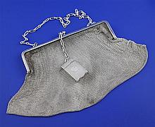 An early 20th century continental silver chain mesh evening handbag with a 1920's silver compact attached, gross weight 9 oz.