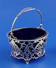 A George V pierced silver sugar basket with blue glass liner, width 4.25in.