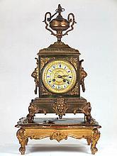 Reloj de mesa de bronce dorado rematado en una copa sobre base. Con péndulo