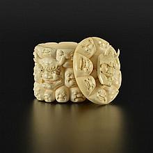 Boîte ovale en ivoire au décor de masques signée G