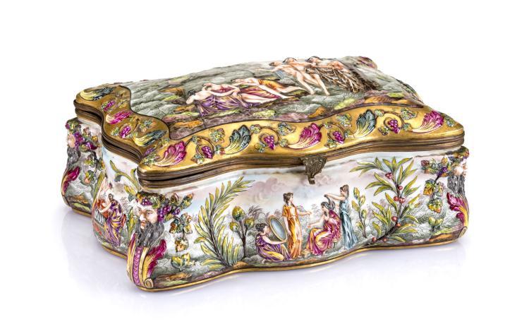 Grand coffret en porcelaine de Capodimonte , XIXe s. De forme mouvementée, à décor en léger relief émaillé de scènes à l'antique, 33,5x21,5x16,5 cm