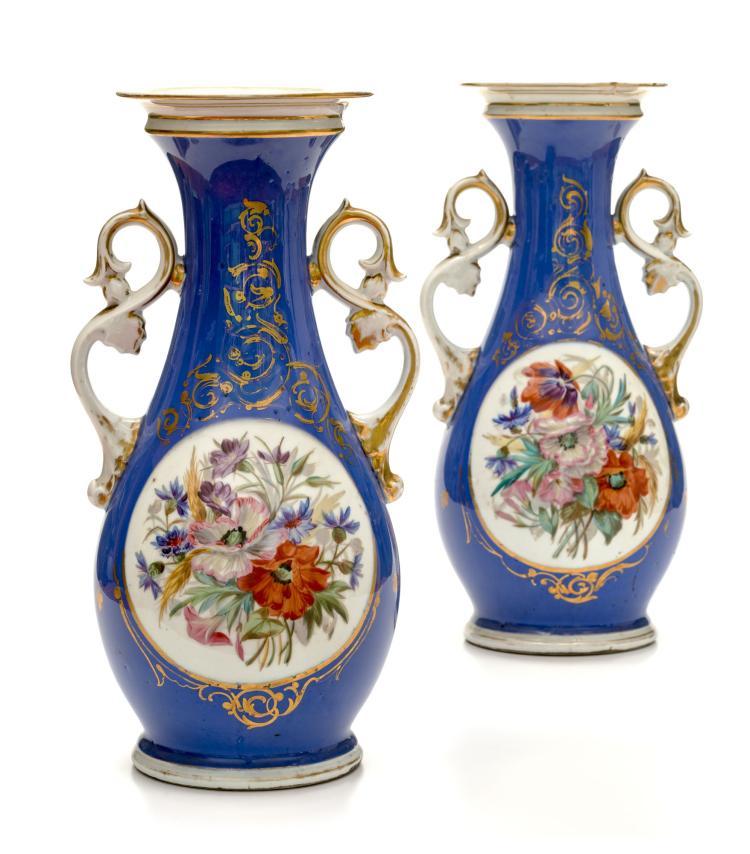 Paire de vases balustres en porcelaine bleue et or. A décor de fleurs, les anses en feuilles d'acanthes, h. 40 cm
