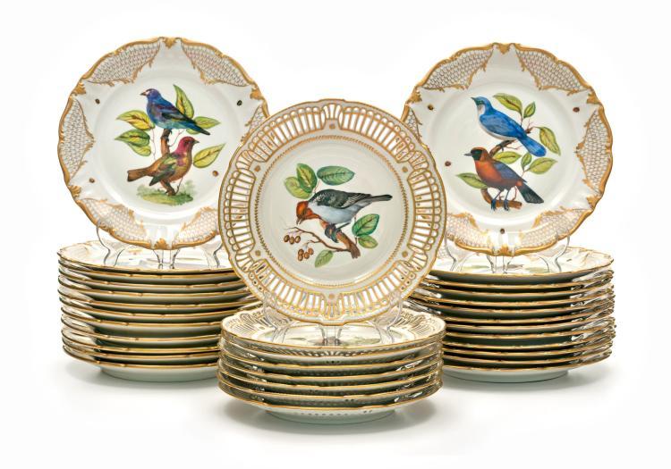 Suite de 32 assiettes en porcelaine. Décor d'oiseaux et bordures or, dont 8 ajourées, diam. 24 et 25,5 cm (lacunes à l'émail)