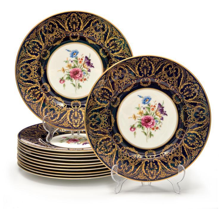 12 assiettes en porcelaine Royal Worcester, années 1950. A décor de bouquet de fleurs polychromes, le marli à motif doré de rinceaux, diam. 27 cm