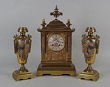 A late 19th century French brass clock garniture