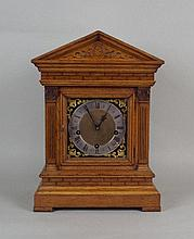A late Victorian oak cased chiming mantel clock of