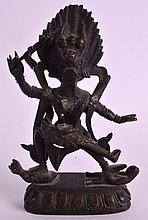 AN 18TH/19TH CENTURY SINO TIBETAN BRONZE FIGURE OF A GOD modelled holding a staff standing upon buddhistic figures. 5.75ins high.