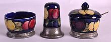 A RARE EARLY 20TH CENTURY MOORCROFT TUDRIC CRUET SET comprising of pepperette, salt cellar & mustard pot. (3)