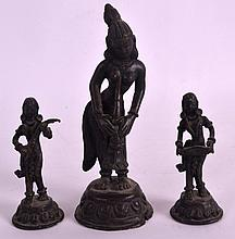 A 19TH CENTURY INDIAN BRONZE FIGURE OF A FEMALE together with a smaller similar pair. 6.5ins & 3.75ins high. (3)