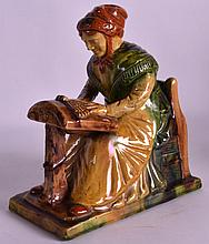 A 19TH CENTURY EUROPEAN MAJOLICA FIGURE OF A FEMALE modelled seated. 8Ins wide.