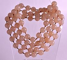 AN EARLY 20TH CENTURY CARVED AGATE TYPE NECKLACE of uniform size. 4Ft 8ins long overall.