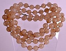 AN EARLY 20TH CENTURY CARVED AGATE TYPE NECKLACE of uniform size. 5Ft long.