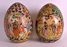 A PAIR OF JAPANESE TAISHO PERIOD PORCELAIN EGGS painted with geishas and figures within landscapes. 12Ins high.