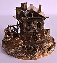 A VICTORIAN GILT BRONZE INKWELL in the form of a house upon a naturalistic base. 8.75ins wide.