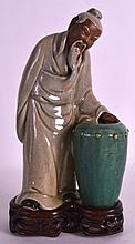A 19TH CENTURY CHINESE POTTERY MODEL OF A SCHOLAR modelled standing beside a green glazed urn. 9.75ins high.