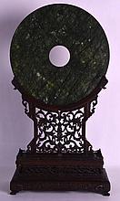 A LARGE CHINESE QING DYNASTY CARVED HARDWOOD FRAMED JADE BI DISC of large proportions. Jade 12ins diameter.