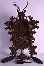 AN EARLY 20TH CENTURY BLACK FOREST BAVARIAN WALL CUCKOO CLOCK carved with a stag, a pair of hounds & motifs. 2Ft 2ins x 1ft 6ins.