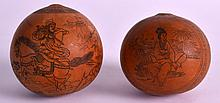 A PAIR OF EARLY 20TH CENTURY CHINESE ENGRAVED NUTS decorated with figures and landscapes. 2ins diameter.