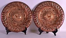 A PAIR OF LATE 19TH CENTURY HISPANO MORESQUE CIRCULAR CHARGERS painted in iron red foliage and a central motif. 1Ft 3ins diameter.