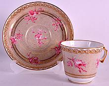 A LATE 19TH CENTURY SEVRES PORCELAIN TEACUP AND SAUCER painted with pink flowers upon a gilt ground.