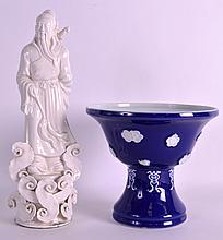 AN EARLY 20TH CENTURY CHINESE BLANC DE CHINE PORCELAIN FIGURE together with a Meiji period blue glazed stem cup. 11.5ins & 6ins high. (2)