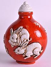 AN EARLY 20TH CENTURY CHINESE CORAL GROUND SNUFF BOTTLE AND STOPPER bearing Daoguang marks to base, decorated in relief with rabbits. 2.5ins high.
