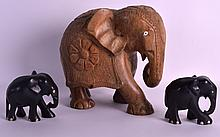 AN EARLY 20TH CENTURY AFRICAN CARVED WOOD FIGURE OF AN ELEPHANT together with two carved ebony elephants. Largest 7.5ins wide. (3)