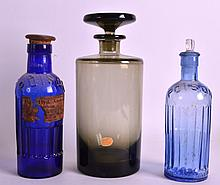 A BOHEMIAN SMOKEY GLASS JAR AND COVER together with two poison jars. Largest 9.5ins high.