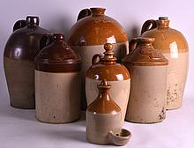 A LARGE 19TH CENTURY STONEWARE ALE BARREL together with six other flagons, including of local interest. Largest 1ft 3.5ins high. (7)