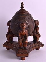 A LATE 19TH CENTURY CARVED AFRICAN COCONUT SHELL ON STAND with figural supports, carved with flowers. 10.75ins high.