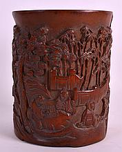 A CHINESE CARVED BAMBOO BRUSH POT Bitong, Late Qing/Republic, decorated with scholars within a landscape. 5.25ins high.
