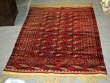 A PERSIAN RED GROUND CARPET decorated with a run of three central motifs within a geometric border. 5Ft 4ins x 4ft 2ins.
