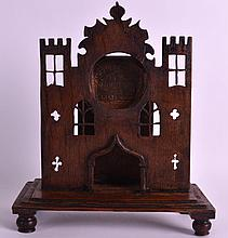 A 19TH CENTURY EUROPEAN CARVED OAK WATCH HOLDER in the form of a castle. 9.5ins x 7.5ins.
